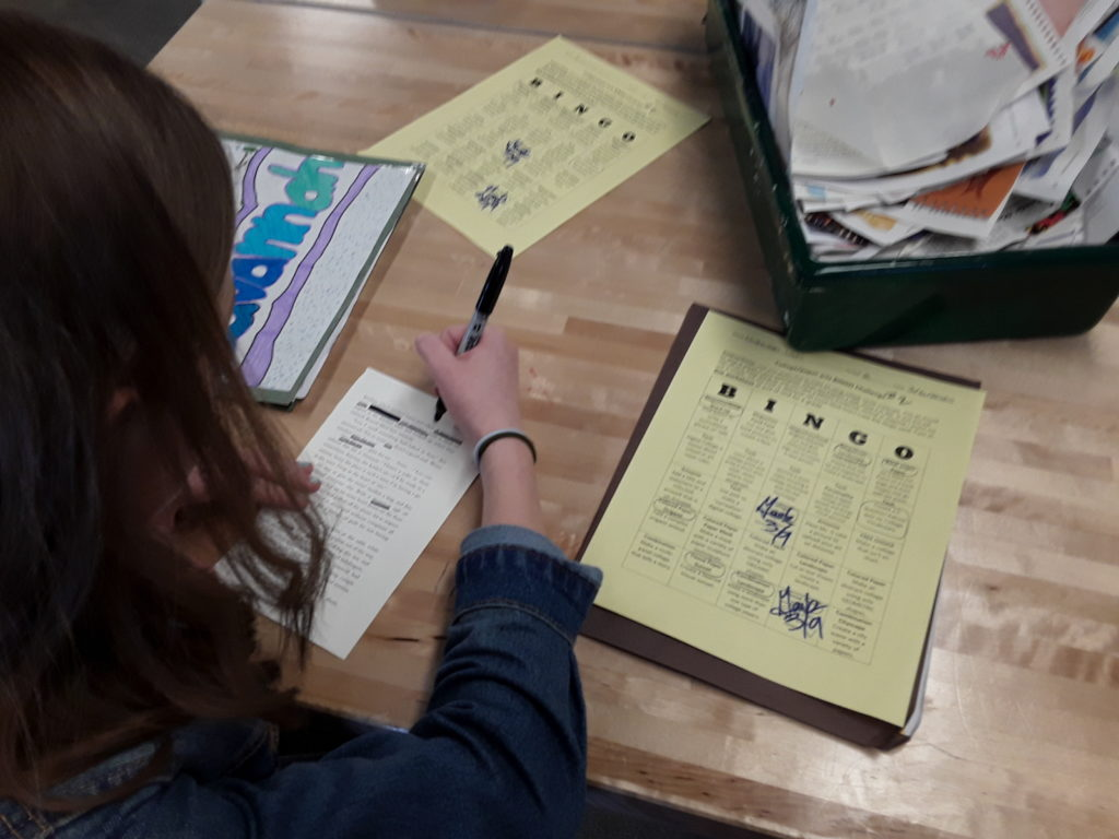 student working on black out poem with bingo card visible